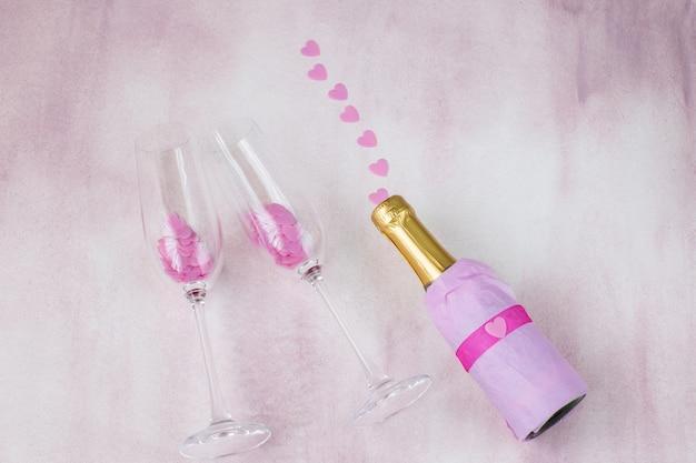 Sobre un fondo rosa una botella de champán y corazones rosados - despedida de soltera Foto Premium