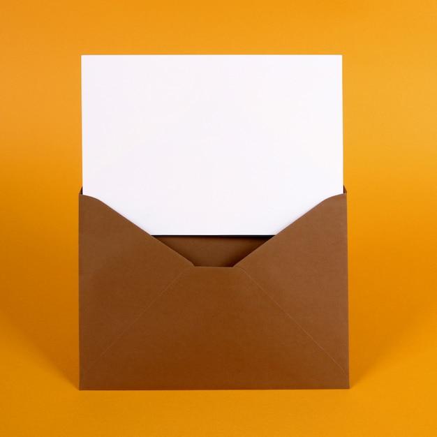 Sobre marrón con tarjeta de mensaje en blanco Foto Premium