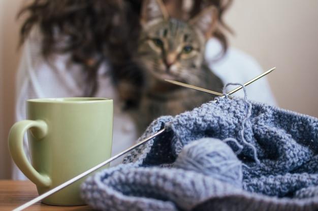 Sobre la mesa hay un tejido y una copa, una niña y un gato. Foto Premium
