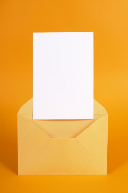 Sobre metálico dorado con tarjeta de mensaje en blanco o invitación. Foto gratis