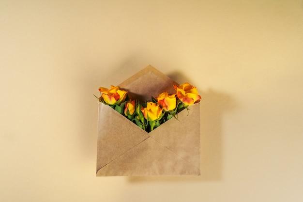 Sobre de papel artesanal con rosas amarillas sobre superficie beige Foto Premium