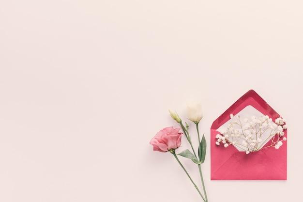 Sobre rojo con ramas de flores en la mesa Foto gratis