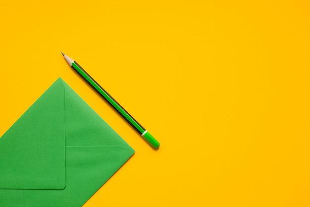 Sobre verde y lápiz verde simple en un fondo amarillo, visión superior, con el copyspace. Foto Premium