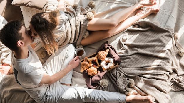 Una sobrecarga de una joven pareja besándose mientras desayunan en la cama Foto gratis