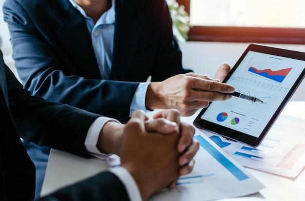 Socio del equipo de inversores del hombre de negocios que piensa y planea sobre información de gráficos de estadísticas financieras Foto Premium