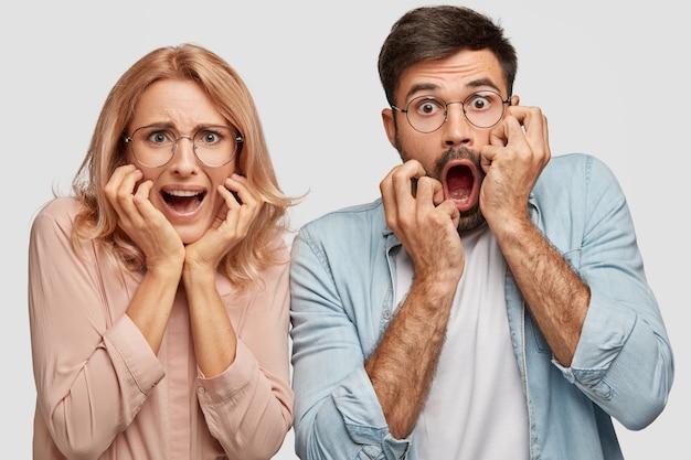 Los socios comerciales de la mujer y el hombre asustados nerviosos desconcertados reaccionan al reducir las ventas y tener deudas financieras Foto gratis