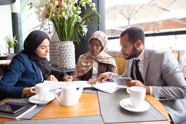 Socios comerciales multiculturales discutiendo contrato en café Foto gratis