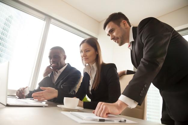 Socios comerciales multirraciales que usan una computadora portátil durante la reunión, miran Foto gratis