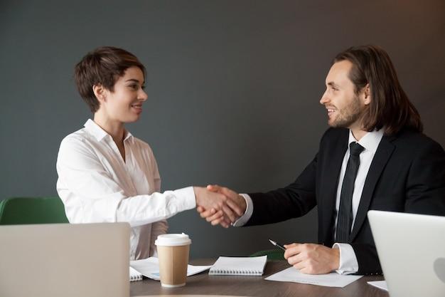 Socios comerciales que saludan con apretón de manos durante la reunión de la oficina Foto gratis