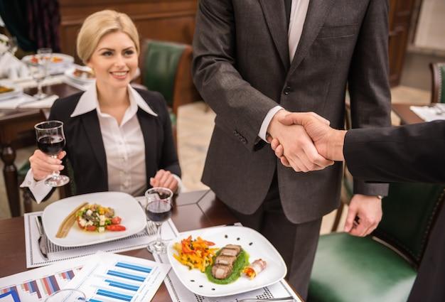 Socios que se dan la mano mientras almuerzan negocios. Foto Premium