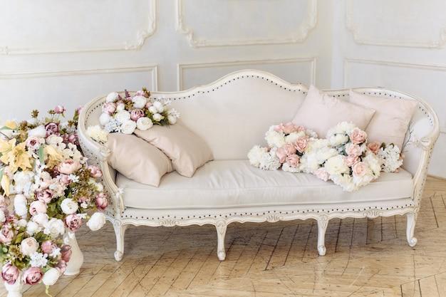 Sofá de color beige claro en colores delicados junto a una gran cantidad de flores, rosas y peonías. Foto Premium