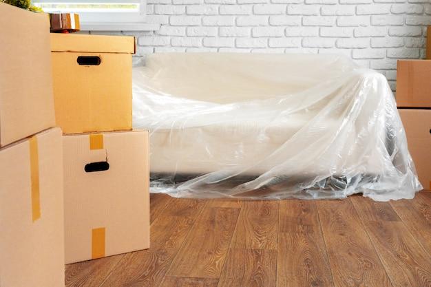 Sofá lleno y pila de cajas de cartón en una habitación, concepto de mudanza Foto Premium