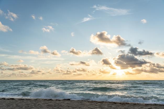 Sol naciente en el horizonte sobre un océano o mar. en el cielo azul nubes blancas Foto Premium