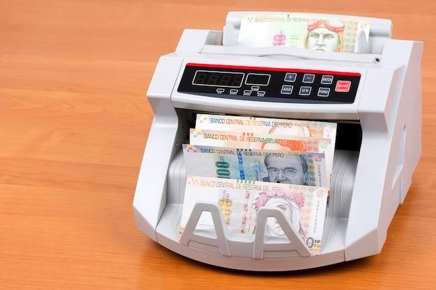 Sol peruano en una máquina de contar Foto Premium