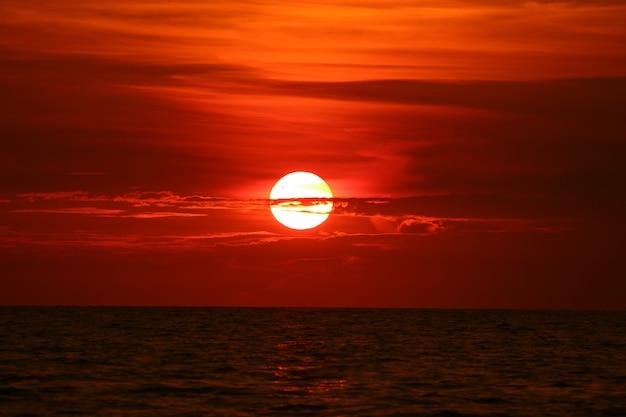 Sol de vuelta en la puesta de sol cielo horizonte ola en superficie mar Foto Premium
