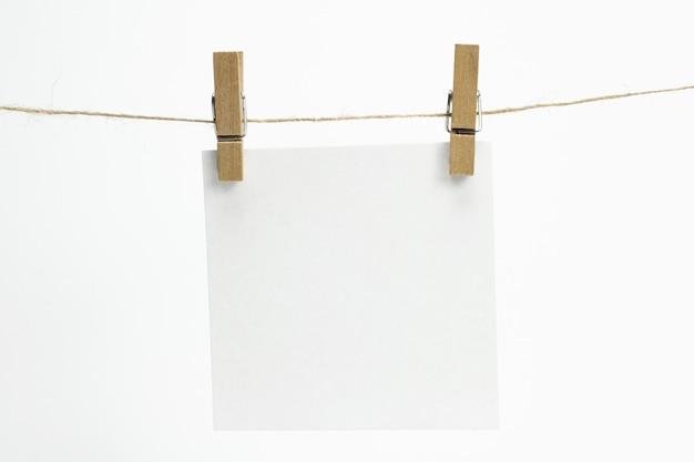 Sola hoja de papel vacía para notas que cuelgan de una cuerda con pinzas para la ropa y aisladas en blanco. Foto gratis