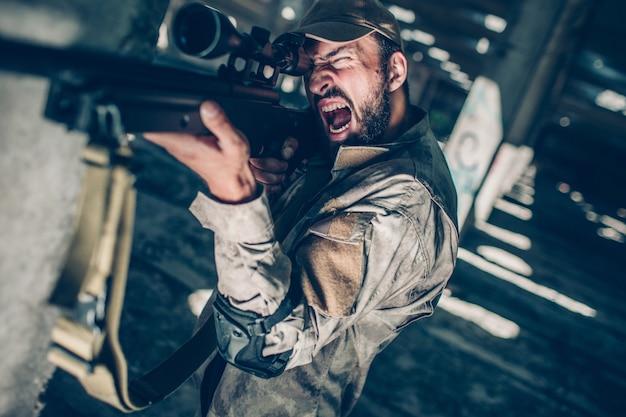El soldado está batiendo. él está mirando a través de la lente porque está apuntando. guy es confiable para disparar con el rifle. Foto Premium