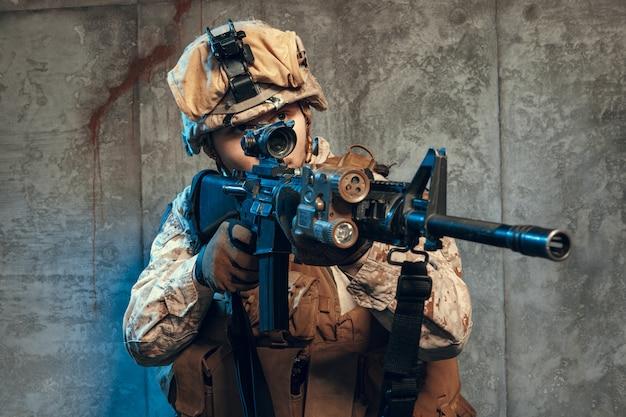 Soldado del ejército totalmente equipado con uniforme de camuflaje y casco, armado con pistola y rifle de asalto Foto Premium