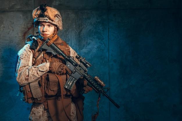 Soldado de las fuerzas especiales de los estados unidos o contratista militar privado con rifle. imagen sobre un fondo oscuro Foto Premium