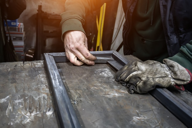 El soldador cocina el marco. el soldador cocina el metal. el soldador cocina estructuras metálicas. trabajos de soldadura. chispas, metal fundido Foto Premium