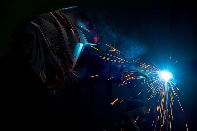 Soldador macho en una máscara de soldadura de metal. foto en colores oscuros. chispas volando. Foto Premium