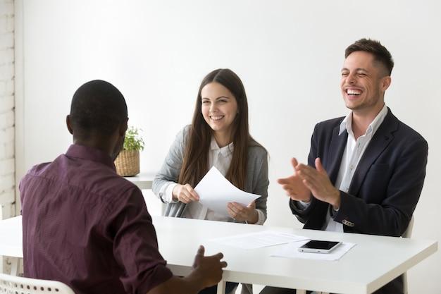 Solicitante africano hacer la risa de la entrevista de trabajo, buena impresión Foto gratis
