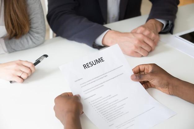 Solicitante afroamericano con currículum en entrevista de trabajo, vista de cerca Foto gratis