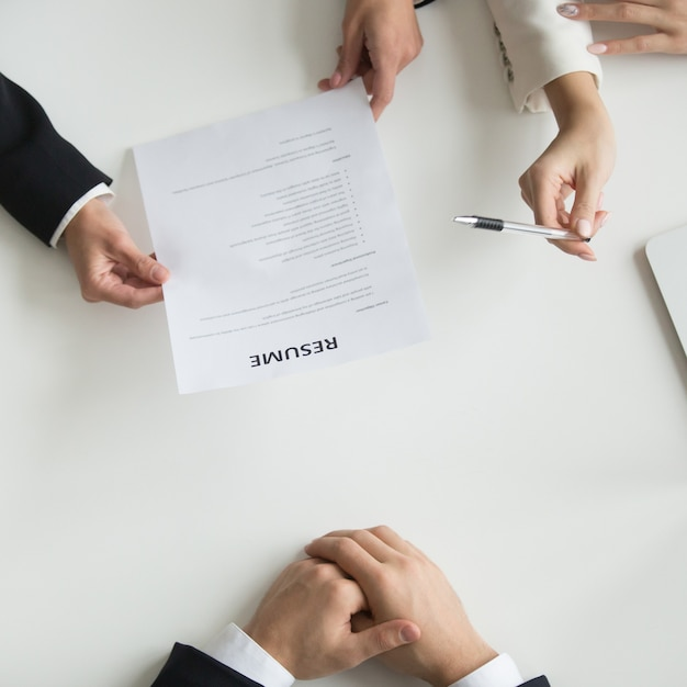 Los solicitantes de lectura de horas reanudan en la entrevista de trabajo, vista superior Foto gratis