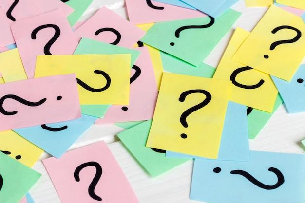 Sólo muchos signos de interrogación en papeles de colores. Foto Premium