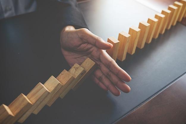 Solución de problemas, close up vista en la mano de la mujer de negocios detener bloques que caen en la mesa de concepto sobre la toma de responsabilidad. Foto gratis