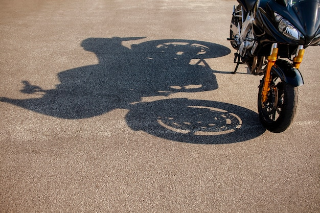 Sombra de moto naranja sobre asfalto Foto gratis