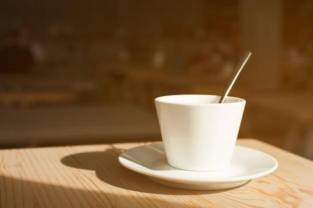Sombra de la taza de café y platillo en el escritorio de madera Foto gratis
