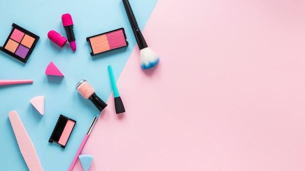 Sombras de ojos con lápiz labial y pincel en polvo sobre mesa Foto gratis