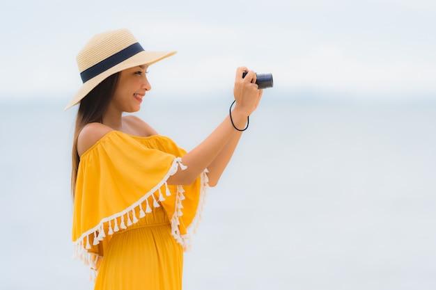 El sombrero asiático hermoso del desgaste de mujer del retrato con ocio feliz de la sonrisa adentro toma una foto en la playa y el mar en vacaciones del día de fiesta Foto gratis