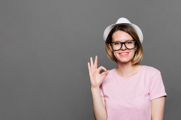 Sombrero blanco que lleva sonriente de la mujer joven que muestra la muestra aceptable contra el contexto gris Foto gratis