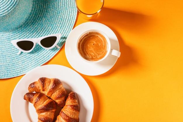 Sombrero, gafas de sol croissant con una taza de café y un vaso de jugo de naranja sobre una mesa amarilla al sol Foto Premium