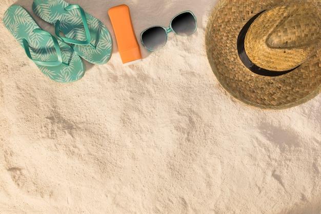 Sombrero gafas de sol sandalias azules y protector solar sobre arena. Foto gratis