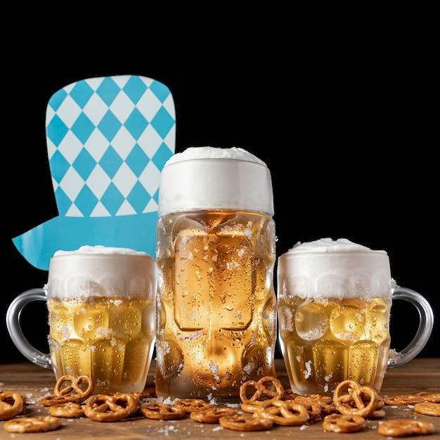 Sombrero oktoberfest con jarras de cerveza y bocadillos. Foto gratis