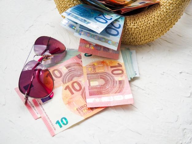 Sombrero de paja, dinero, tarjetas bancarias, anteojos. Foto Premium