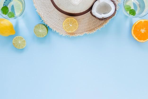 Sombrero de paja con frutas exóticas en mesa. Foto gratis