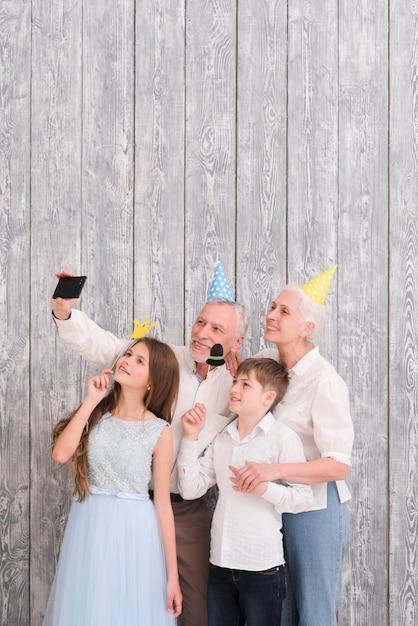 Sombrero del partido que lleva del abuelo que toma el selfie en el teléfono móvil con sus nietos que sostienen los apoyos de papel Foto gratis