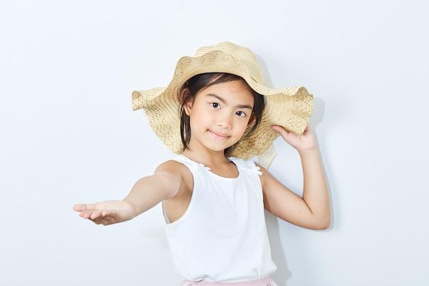 Sombrero que lleva de la muchacha delgada asiática en el fondo blanco. Foto Premium