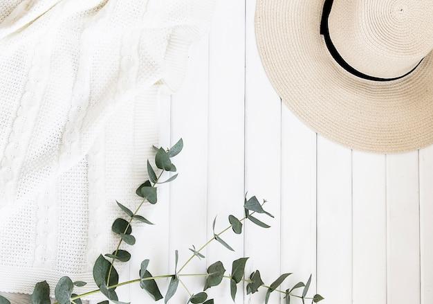Sombrero de verano y hojas de eucalipto sobre un fondo claro. Foto gratis