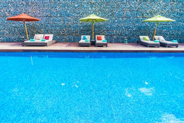 Sombrilla y silla alrededor de la piscina. Foto gratis