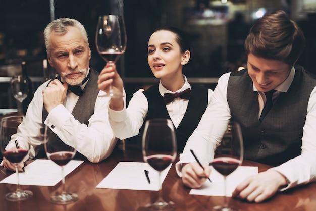 Sommeliers es dos hombres y una mujer en el restaurante. Foto Premium