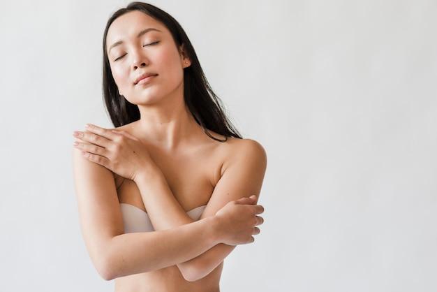 Soñadora mujer asiática en sujetador abrazándose Foto gratis