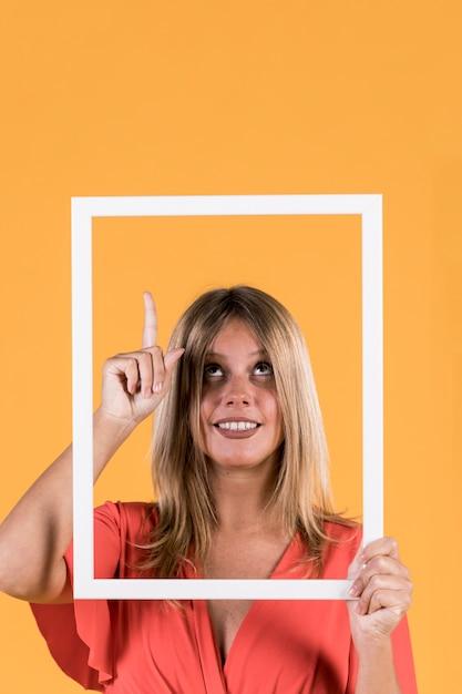 Sonriendo deshabilitar mujer sosteniendo recorte de marco con apuntando hacia arriba en superficie plana Foto gratis