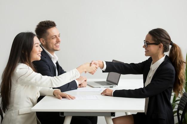 Sonriendo diversas empresarias dan la mano en la reunión del grupo, concepto de trato Foto gratis