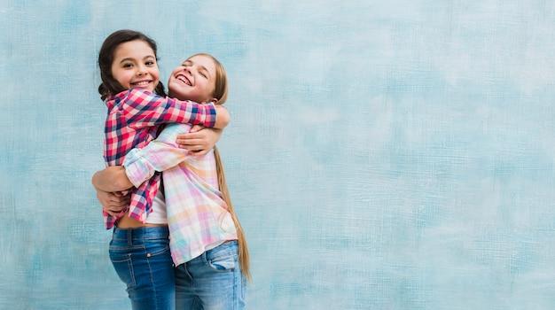 Sonriendo dos chicas abrazando de pie contra la pared pintada de azul Foto gratis