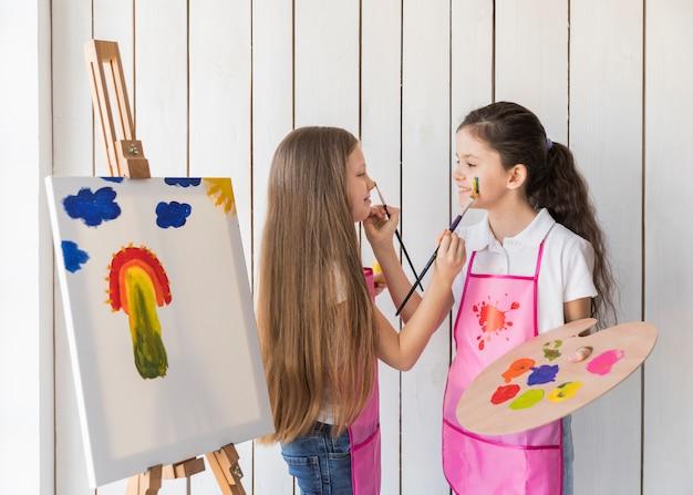 Sonriendo dos niñas pintándose cara a cara con un pincel de pie cerca del lienzo Foto gratis